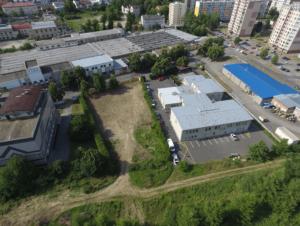 Pohled z výšky na sídliště s panelovými domy, zelení a auty